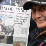 Former Xeni Gwet'in Band Councillor Gilbert Solomon proudly displays a copy of the Vancouver Sun, featuring Chief Marilyn Baptiste, on the day the Tsilhqot'in learned of their victory at the BC Supreme Court