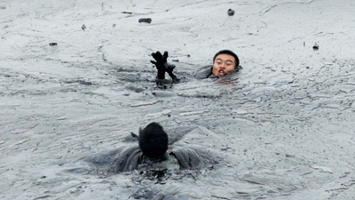 Workers attempt to rescue a firefighter from drowning in the oil slick during the oil spill clean-up operations at Dalian's Port on July 20, 2010. (REUTERS/Jiang  He/Greenpeace)