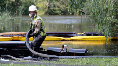 A worker from Enbridge skims oil off the surface of the Kalamazoo River after a pipeline ruptured in Marshall, Michigan. (July 27, 2010) - photo Andre J. Jackson/MCT